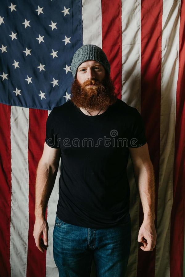 Man with beard staring in front of an American Flag stock photography