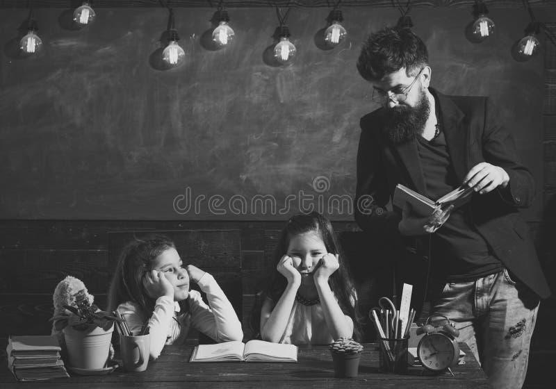 Man with beard teaches schoolgirls, reading book. Bored and tired children listening teacher. Teacher and girls pupils stock image