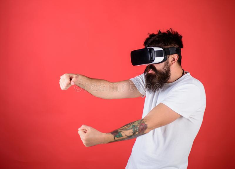 Man with beard in VR glasses driving car, red background. Virtual racing concept. Guy play racing game in VR. Hipster on royalty free stock image