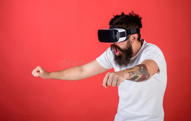Man with beard in VR glasses driving motorbike, red background. Hipster on shocked face driving bike on high speed in royalty free stock photos