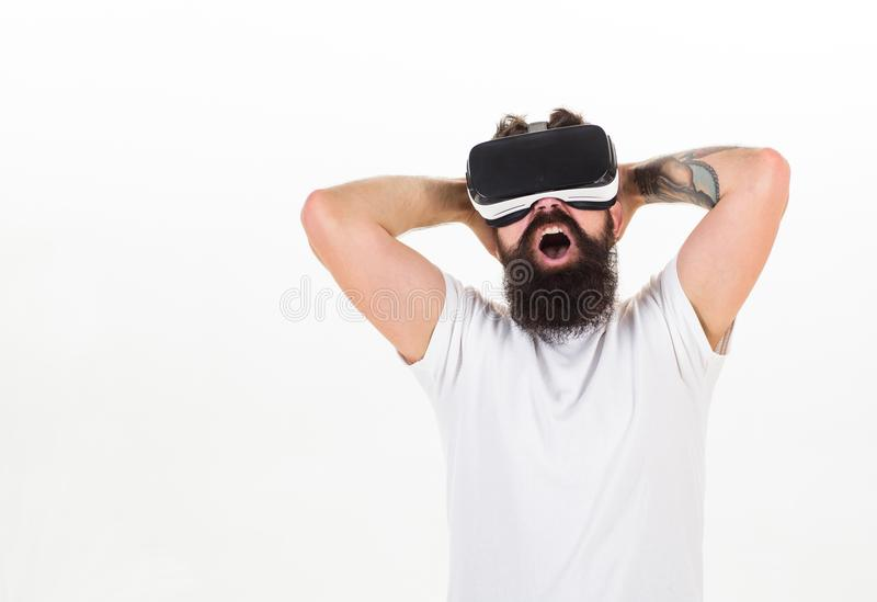 Man with beard in VR glasses enjoy watching video, white background. Virtual cinema concept. Hipster on excited face royalty free stock photo