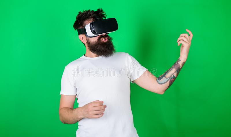 Man with beard in VR glasses, green background. Hipster guitarist on enthusiastic face use modern technology for. Entertainment. Guy with VR glasses learn to stock photos