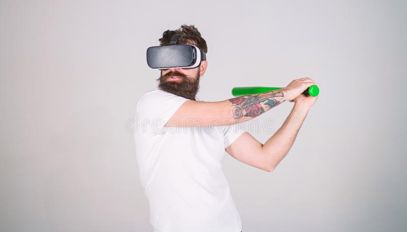 Man with beard in VR glasses, grey background. Hipster on concentrated face use modern technologies for sporty. Entertainment. VR sportsman concept. Guy with VR royalty free stock image