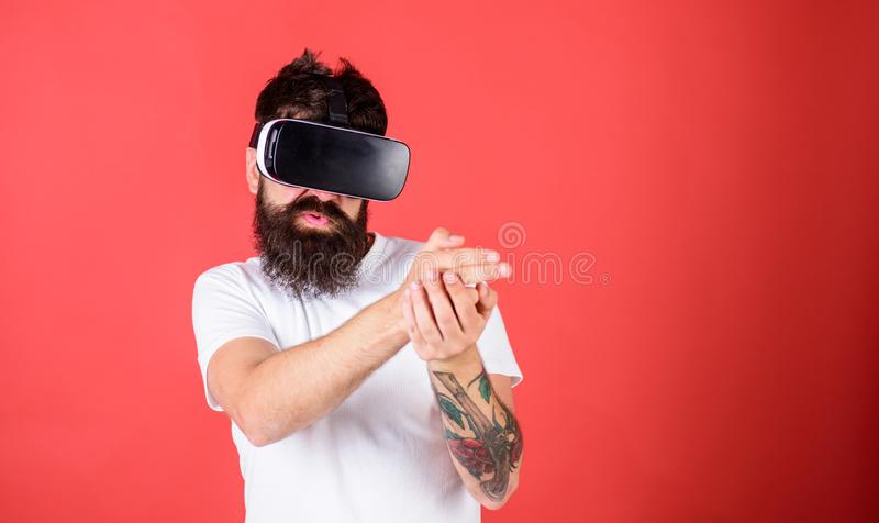 Man with beard in VR glasses shooting, red background. VR gadget concept. Guy with head mounted display shoot with gun royalty free stock photo