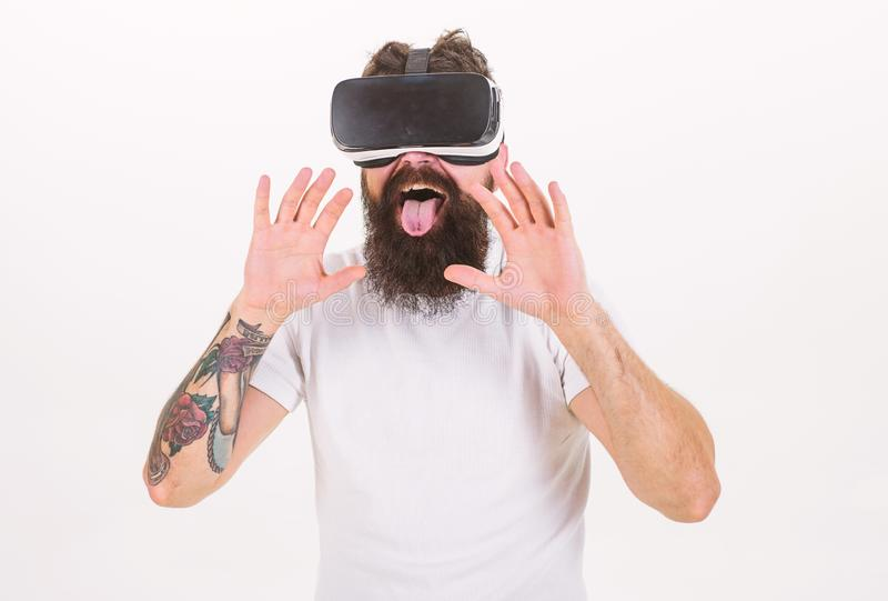 Man with beard in VR glasses, white background. Virtual sex concept. Guy with head mounted display having sex in virtual. Reality. Hipster licking with tongue royalty free stock photos