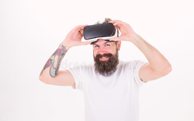 Man with beard in VR goggles smiling isolated on white background. Hipster with tattoed arm and stylish beard ready for. Digital experience. Bearded man testing stock photography