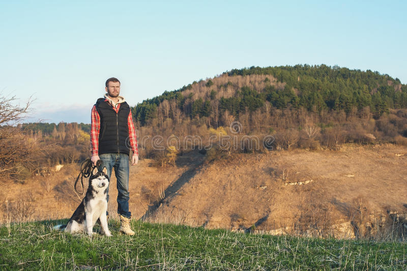 A man with a beard walking his dog in the nature, standing with a backlight at the rising sun, casting a warm glow and. Long shadows against the background of stock photos