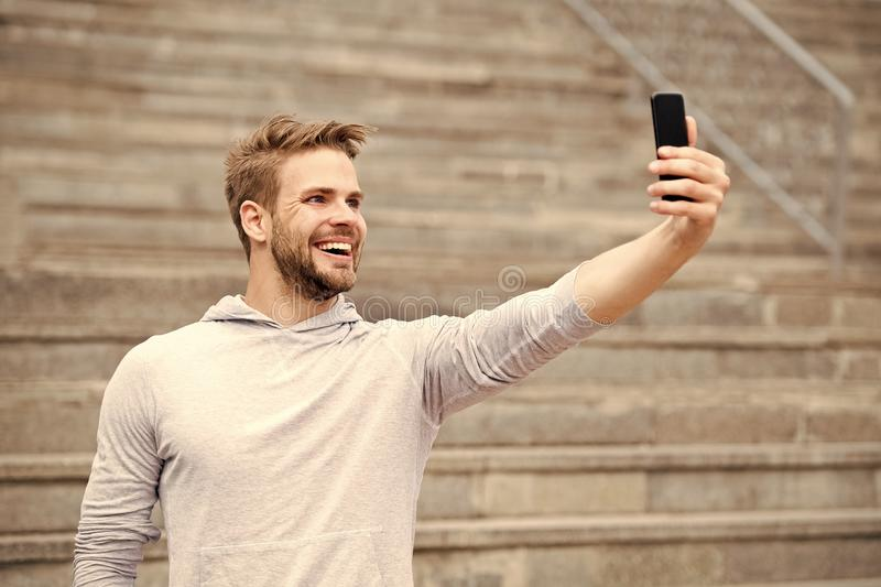 Man with beard walks with smartphone, urban background with stairs. Man blogger using video conferencing on smartphone stock images