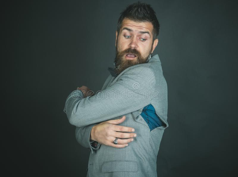 Man with beard wear jacket with hole on dark background. Man with beard wears jacket with hole on dark background. Hipster chose small size jacket, seam torn royalty free stock photo
