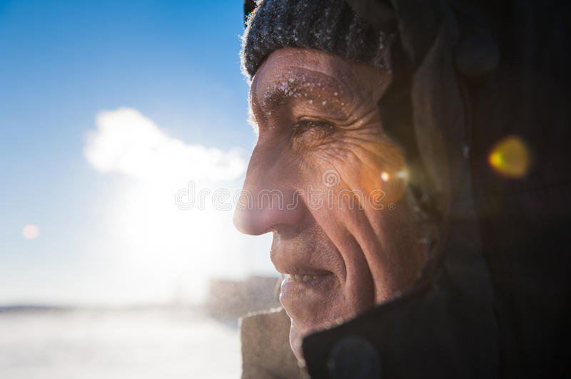 Man with a beard wearing a cap polar explorer a manly strong brutal on the background sky with white clouds wallpaper. Man with a beard wearing a cap with a stock images