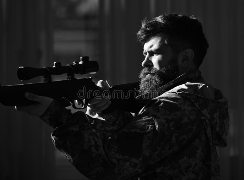 Man with beard wears camouflage clothing, dark interior background. Macho on suffering grimace face aiming at victim royalty free stock photo