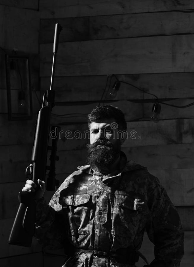 Man with beard wears camouflage clothing, wooden interior background. Macho on strict face at gamekeepers house. Hunter royalty free stock photography