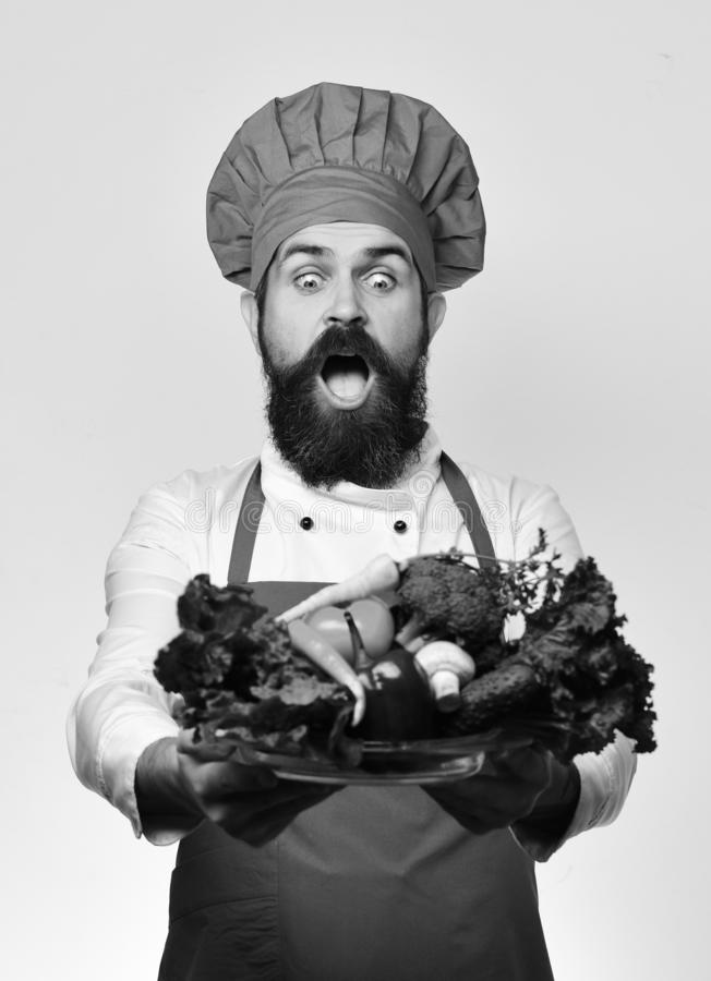 Man with beard on white background. Cook with shocked face. Man with beard isolated on white background. Cook with shocked face in burgundy uniform holds salad royalty free stock image