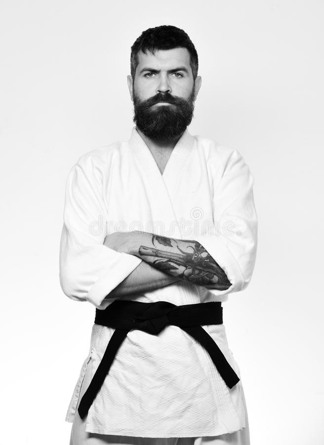 Man with beard in white kimono on white background. Japanese martial arts concept. Taekwondo master with black belt. Holds arms crossed. Karate man with serious royalty free stock photography