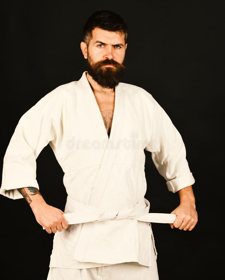 Man with beard in white kimono on black background. Healthy lifestyle and sports concept. Karate man with strict face in uniform. Jiu Jitsu master ties white royalty free stock photo