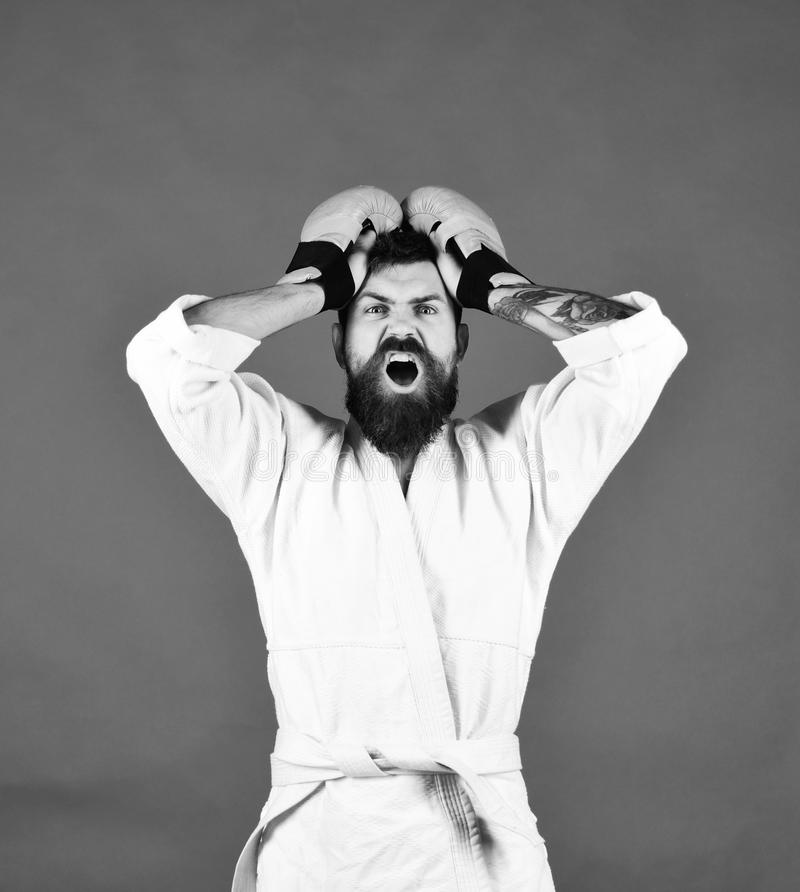 Man with beard in white kimono on green background. Karate man with shocked face in uniform and boxing gloves. Combat master has holds hands on head in royalty free stock images