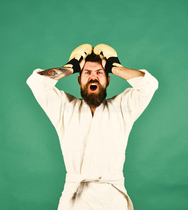 Man with beard in white kimono on green background. Karate man with shocked face in uniform and boxing gloves. Combat master has holds hands on head in stock photo