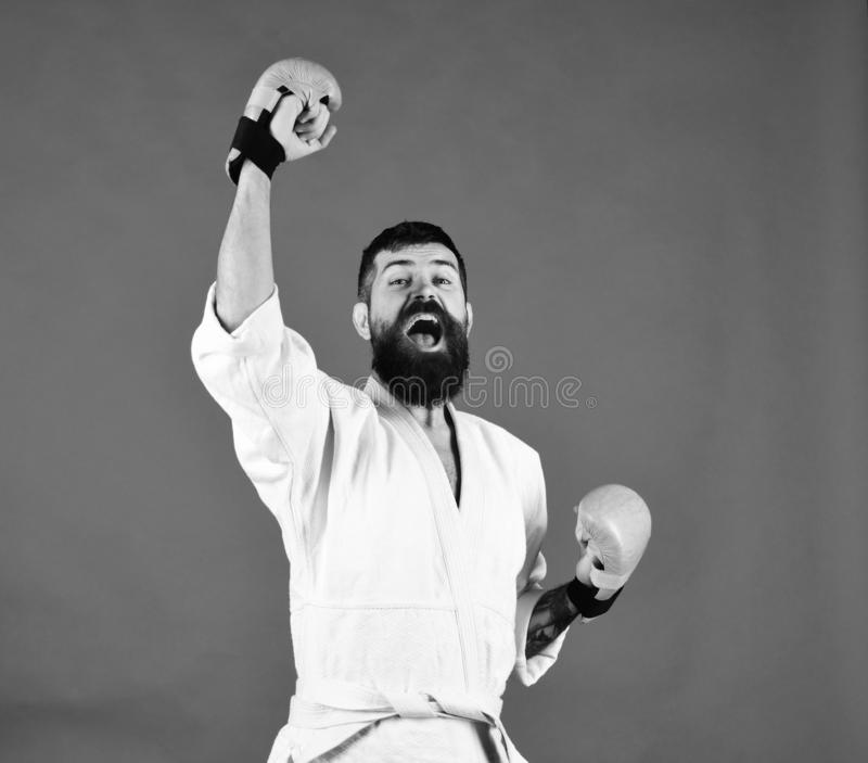 Man with beard in white kimono on green background. Oriental sports concept. Combat master holds hands up in victory and yells. Karate man with happy excited royalty free stock photography