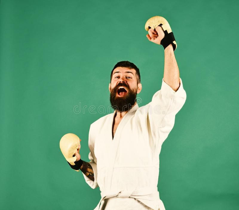 Man with beard in white kimono on green background. Oriental sports concept. Combat master holds hands up in victory and yells. Karate man with happy excited royalty free stock images