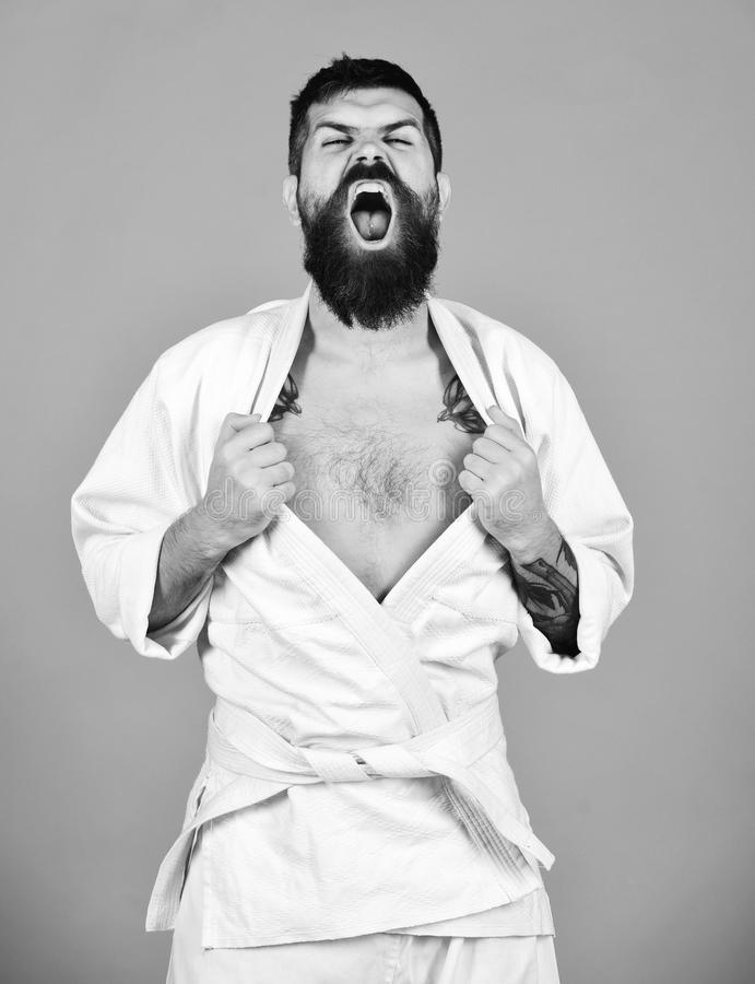 Man with beard in white kimono on red background. Japanese martial arts concept. Karate man with angry face stock photography