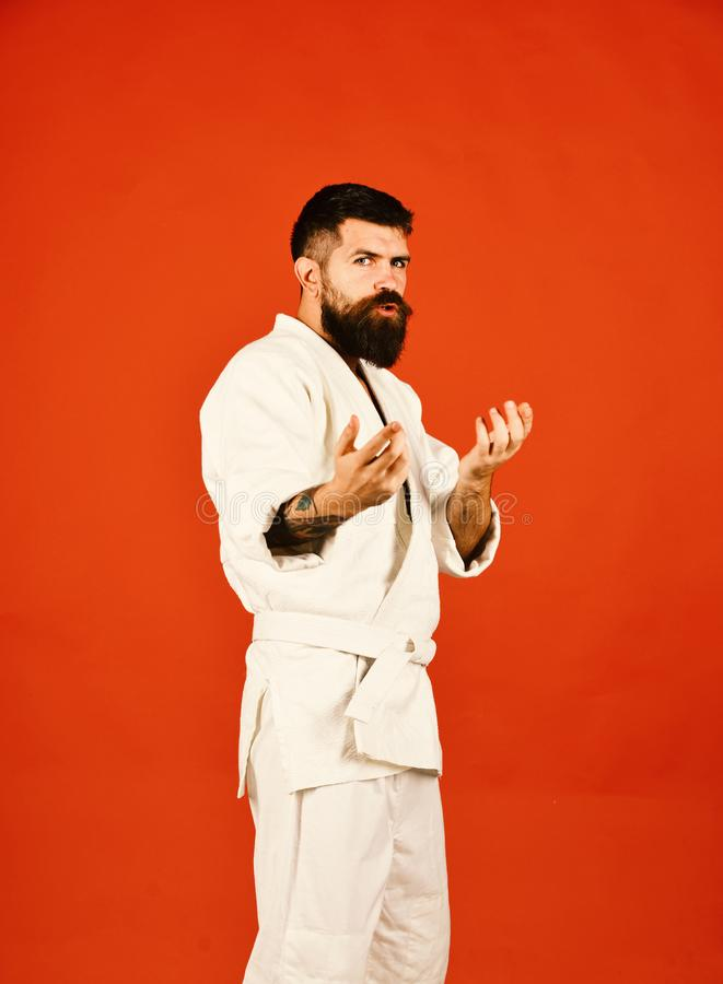 Man with beard in white kimono on red background. Judo master practices attack or defense posture asking for battle. Karate man with concentrated face in royalty free stock photo