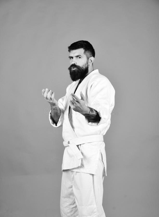 Man with beard in white kimono on red background. Judo master practices attack or defense posture asking for battle. Karate man with concentrated face in stock images