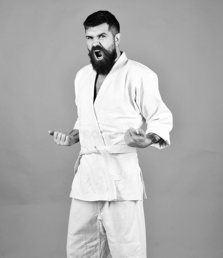 Man with beard in white kimono on red background. Karate man with raging face in uniform. Taekwondo master practices attack posture. Japanese martial arts stock images