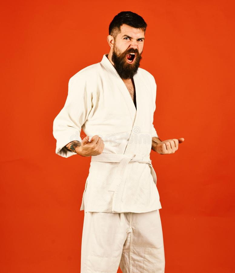 Man with beard in white kimono on red background. Karate man with raging face in uniform. Taekwondo master practices attack posture. Japanese martial arts stock photography