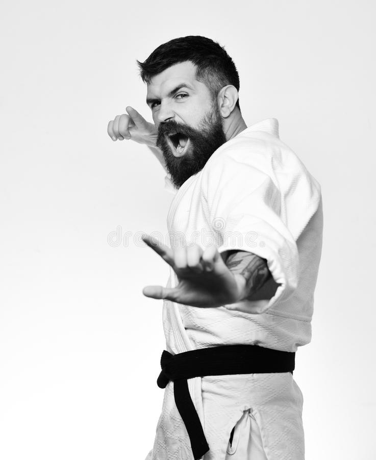 Man with beard in white kimono on white background. Karate man with angry face in uniform. Oriental sports concept. royalty free stock photos