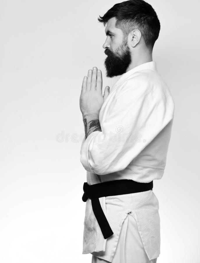 Man with beard in white kimono on white background. Side view. Oriental sports concept. Karate man with serious face in uniform. Jiu Jitsu master with black royalty free stock photography