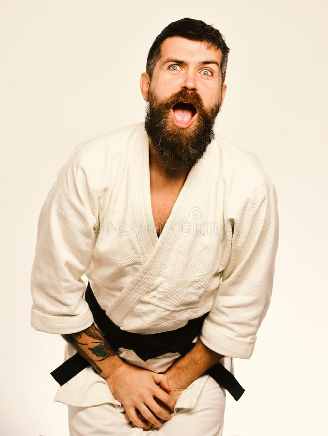 Man with beard in white kimono on white background. Training and combat concept. Jiu Jitsu master got punch into groin covering it with hands. Karate man with stock photos