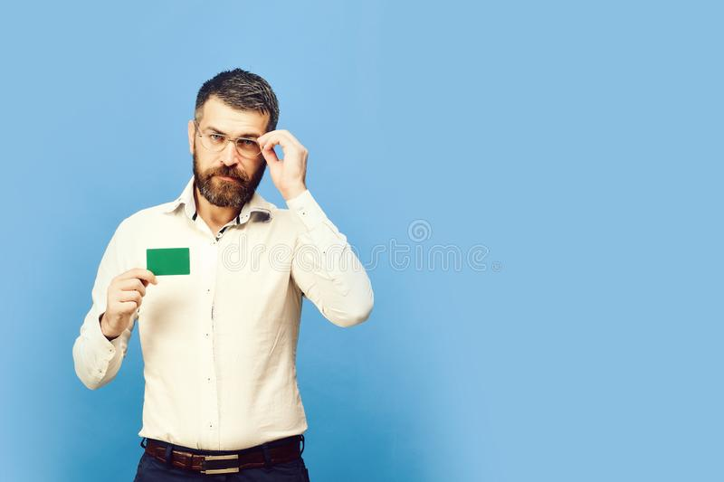 Man with beard in white shirt holds green business card. Guy with smart face with glasses isolated on blue background stock images