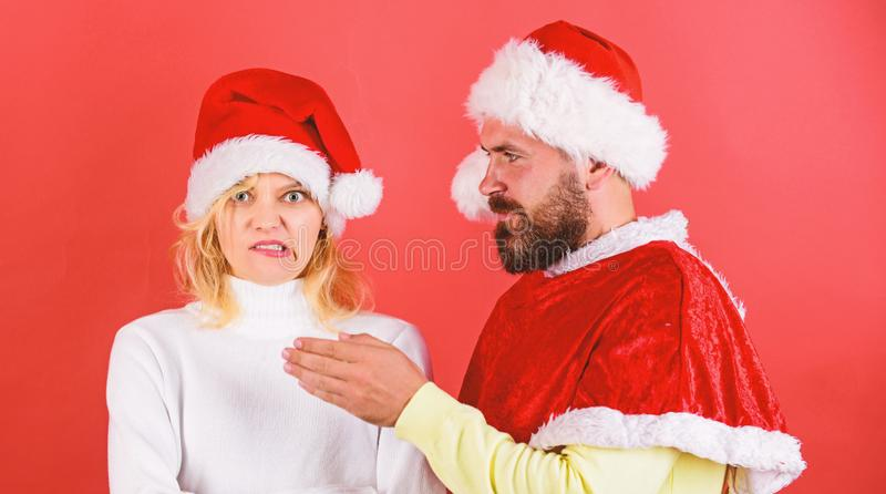 Man with beard and woman in santa hat on red background. Girl disgusted face celebrate christmas. Couple celebrate stock photography