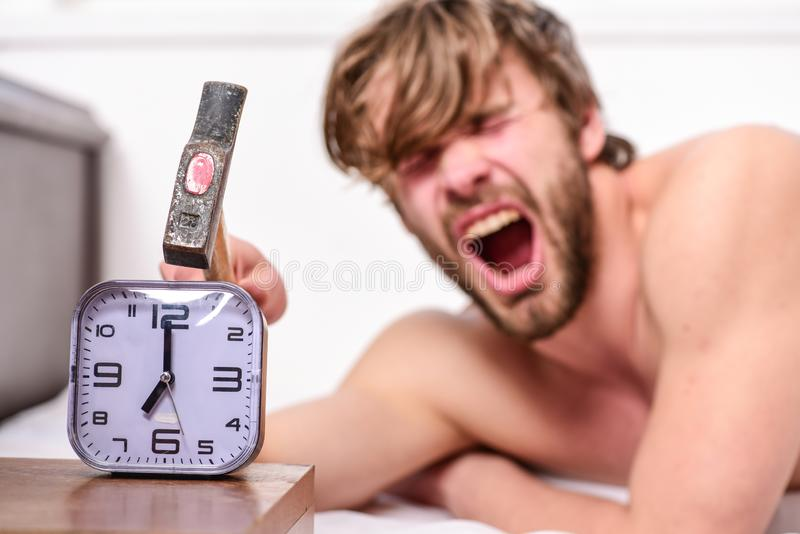 Man bearded annoyed sleepy face lay pillow near alarm clock. Break discipline regime. Stop ringing. Annoying sound. Annoying ringing alarm clock. Guy knocking stock photo