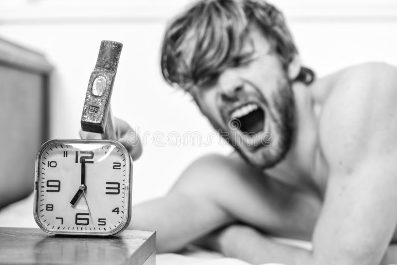 Man bearded annoyed sleepy face lay pillow near alarm clock. Break discipline regime. Stop ringing. Annoying sound. Annoying ringing alarm clock. Guy knocking stock photography