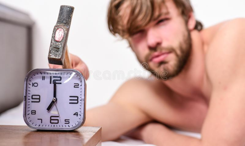 Man bearded annoyed sleepy face lay pillow near alarm clock. Guy knocking with hammer alarm clock ringing. Break. Discipline regime. Stop ringing. Annoying royalty free stock images