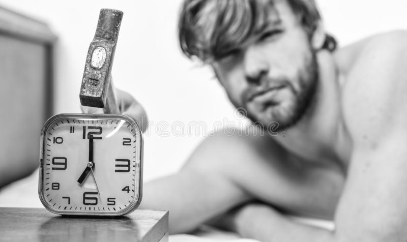 Man bearded annoyed sleepy face lay pillow near alarm clock. Guy knocking with hammer alarm clock ringing. Break. Discipline regime. Stop ringing. Annoying stock images