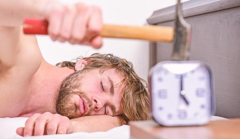 Man bearded annoyed sleepy face lay pillow near alarm clock. Guy knocking with hammer alarm clock ringing. Break. Discipline regime. Annoying sound. Stop royalty free stock photos
