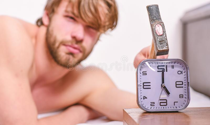 Man bearded annoyed sleepy face lay pillow near alarm clock. Guy knocking with hammer alarm clock ringing. Break. Discipline regime. Stop ringing. Annoying stock photos