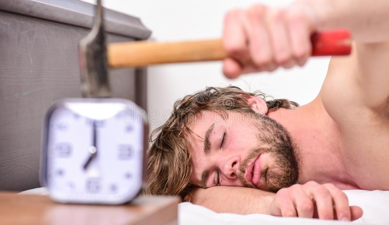 Man bearded annoyed sleepy face lay pillow near alarm clock. Guy knocking with hammer alarm clock ringing. Break. Discipline regime. Annoying sound. Stop stock photos