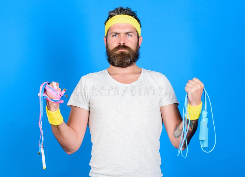 Man bearded athlete hold jump rope and tape measure. Athlete guide stay in shape. Old school aerobics concept. Athlete stock image