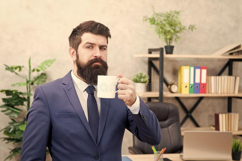 Man bearded businessman hold coffee cup stand office background. Drinking coffee relaxing break. Boss enjoying energy stock photography