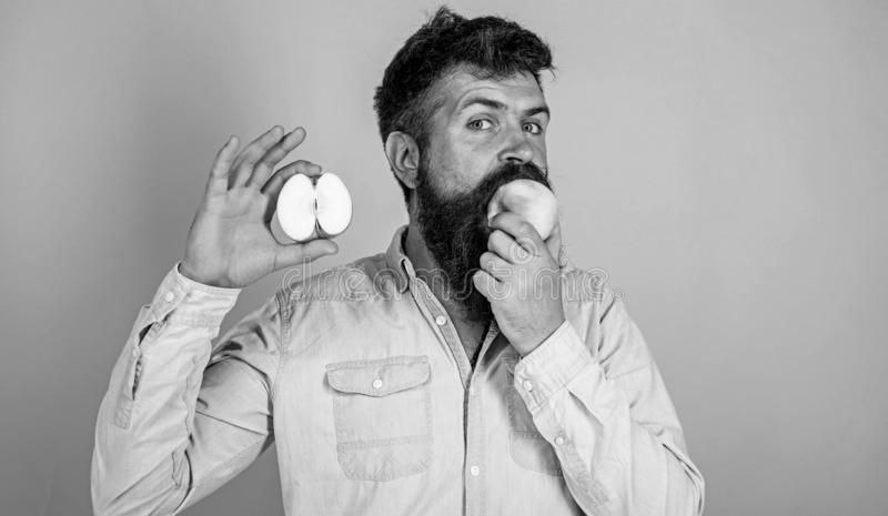 Man bearded eats fruit, holds apple blue background. Half of apple healthy lifestyle. Nutritional value concept. Healthcare dieting vitamin nutrition. Hipster stock images