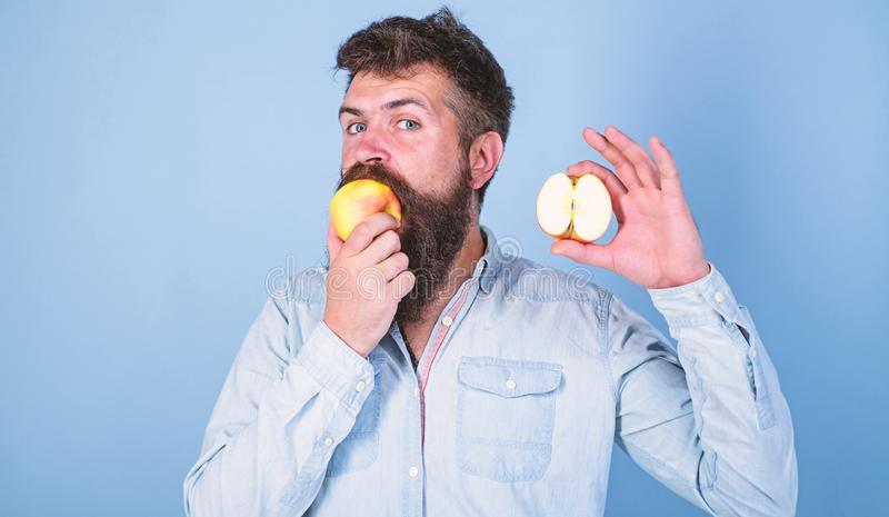 Man bearded eats fruit, holds apple blue background. Half of apple healthy lifestyle. Nutritional value concept. Man bearded eats t, holds apple blue background royalty free stock photo