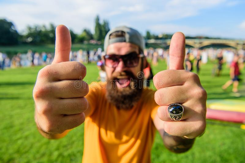 Man bearded in front of crowd riverside background. Book ticket now summer festival. Highly recommend top list events. Hipster visiting event picnic fest or stock photos
