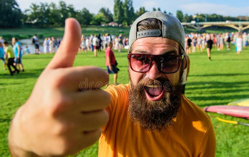 Man bearded in front of crowd riverside background. Man cheerful face shows thumb up. Top list summer festival must. Visit. Hipster visiting event picnic fest royalty free stock photo