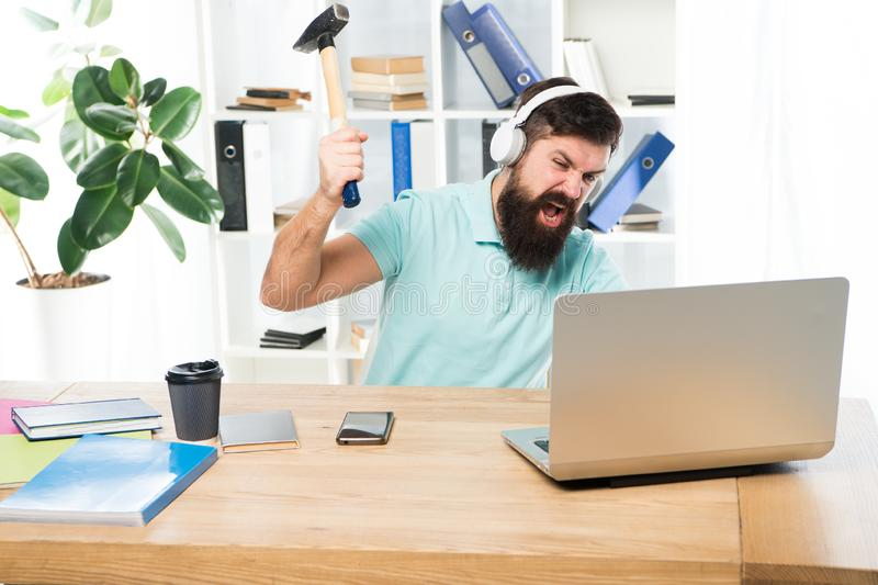 Man bearded guy headphones office swing hammer on computer. Slow internet connection. Outdated software. Computer lag royalty free stock photos