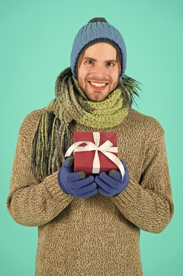 Man bearded handsome wear winter hat scarf gloves hold gift box. Hipster hold christmas gift with bow. Holiday present. Concept. Winter holidays. Give gift stock photography
