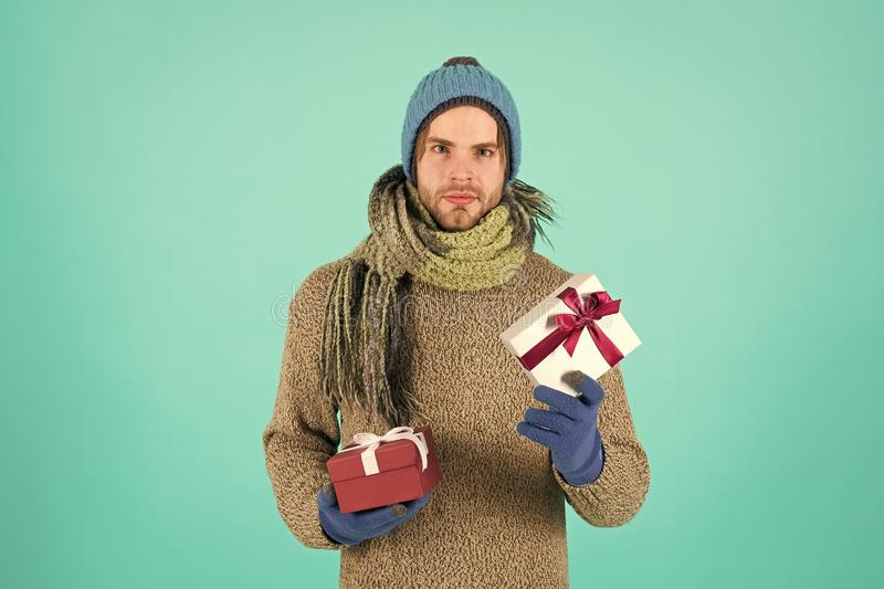 Man bearded handsome wear winter hat scarf gloves hold gift box. Hipster hold christmas gift with bow. Valentines day royalty free stock image