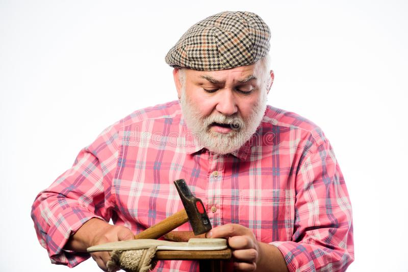 Man bearded handyman working with tools white background. Custom made shoes. Shoe repair shop. Senior master with hammer stock image